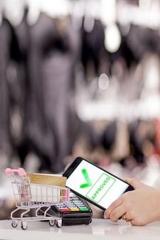 Pos terminal, betalingsmachine met mobiele telefoon op winkelachtergrond. contactloze betaling met nfc-technologie