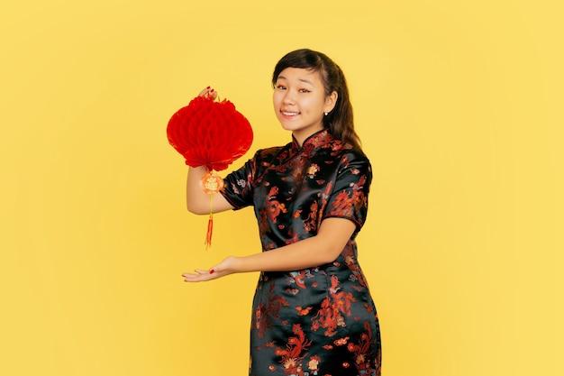 Poseren met lantaarn, lachend, uitnodigend. gelukkig chinees nieuwjaar. aziatisch jong meisjesportret op gele achtergrond. copyspace.