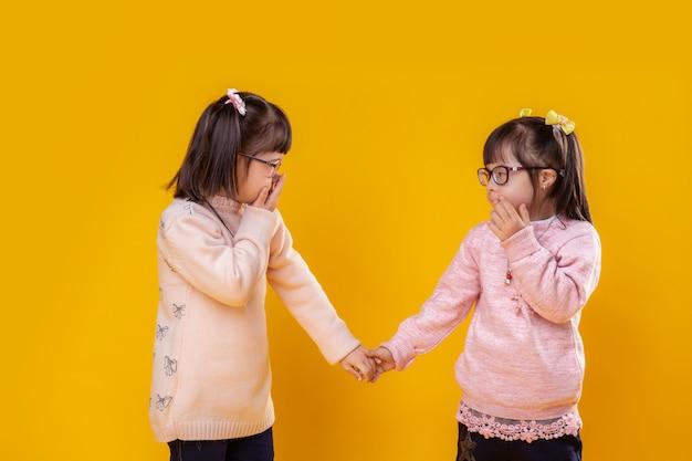 Poseren om te schieten. schattige kleine meisjes die lijden aan chromosoomafwijkingen die elkaar aankijken
