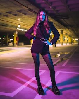 Poseren van een brunette kaukasisch meisje, zittend in een ondergrondse parkeergarage, verlicht met neonlichten