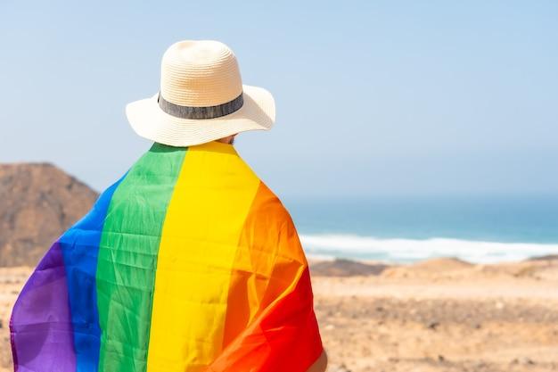 Poseren van een onherkenbare homo met een grijs t-shirt en met de lgbt-vlag aan zee, symbool van homoseksualiteit