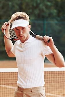 Poseren voor een camera. jonge tennisser in sportieve kleding is buiten op het veld.