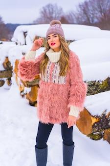 Poserend blond model met roze bontjasje en paarse hoed in de sneeuw. naast enkele bomen die met ijs zijn gekapt, winterlevensstijl
