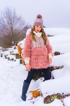 Poserend blond model met roze bontjasje en paarse hoed in de sneeuw. naast enkele met ijs gekapte bomen op een voetpad, winterlevensstijl