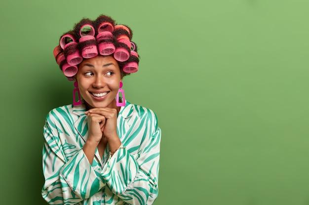 Positief, aangenaam ogende dame houdt de handen onder de kin, lacht breed en kijkt weg, draagt haarrollers voor het maken van krullend haar, gekleed in huiselijke kleding, denkt aan iets aangenaams