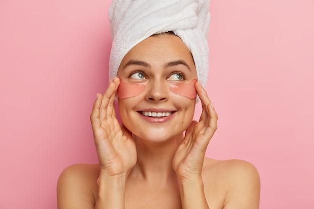 Positief, aangenaam ogende vrouw geeft om ogen huid schoonheid, appiles hydraterende collageen vlekken op gezicht, kijkt opzij, staat topless, heeft schoonheidsbehandelingen na het nemen van bad, verwijdert rimpels