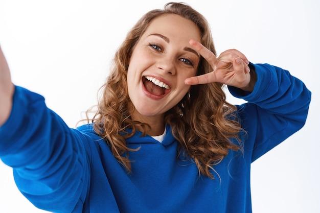 Positief aantrekkelijk meisje dat selfie neemt, v-teken vredesgebaar in de buurt van oog toont en camera vasthoudt met gestrekte hand, foto maakt op smartphone, witte muur