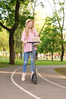 Positief aantrekkelijk meisje met een scooter op een zomerse wandeling in het park zomervakantie