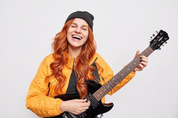 Positief aantrekkelijk tienermeisje getalenteerde populaire zangeres speelt akoestische gitaar presenteert haar nieuwe rocknummer heeft lang gemberhaar draagt hoed oranje jas
