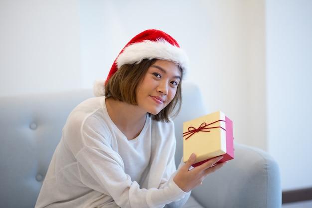Positief aziatisch meisje in santa glb die gift tonen