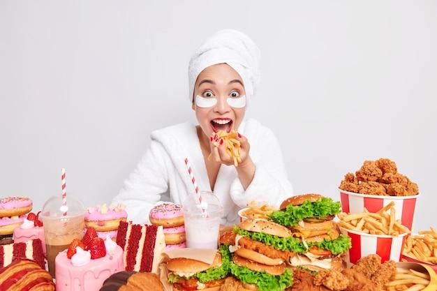 Positief aziatisch vrouwelijk model eet friet en consumeert junkfood