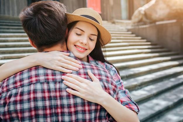 Positief beeld dat van jonge vrouw haar man omhelst. ze glimlacht en houdt de ogen gesloten. ze draagt een hoed. ze staan op trappen.