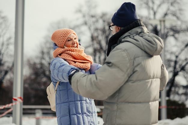 Positief bejaarde echtpaar in winterkleren dat actieve tijd buitenshuis doorbrengt en handen vasthoudt tijdens het dansen