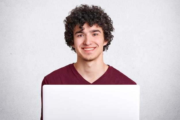 Positief blij man met knapperig haar, gekleed in casual t-shirt, heeft een charmante glimlach, maakt gebruik van moderne laptopcomputer voor het zoeken naar internet, geïsoleerd op wit. mensen en technologie concept