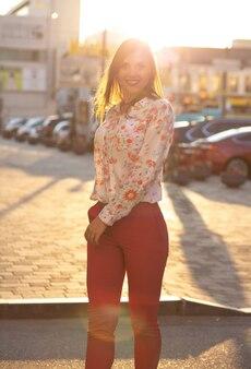 Positief brunette model met blouse en roze jas die zich voordeed op de achtergrond van de avondstad