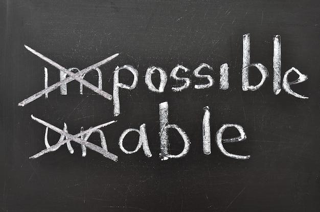 Positief denken concept handgeschreven op zwart bord met gewijzigd onmogelijk