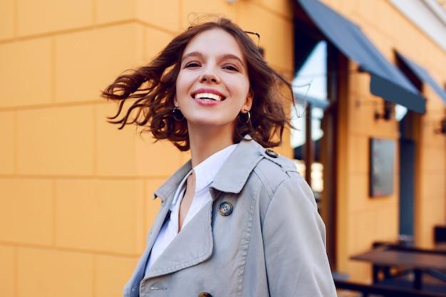 Positief dicht omhooggaand portret van glimlachend gelukkig kortharig meisje met perfecte witte tanden die pret hebben. winderige haren. herfst stemming.