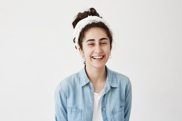 Positief, emotioneel donkerharig vrouwelijk model draagt een spijkerblouse met een brede glimlach, lacht om de grap, verheugt zich over haar leven en herinnert zich aangename momenten met haar vriend. schoonheid, geluk en jeugd