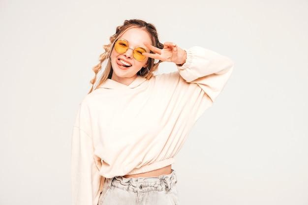 Positief en grappig model poseren op grijze muur in studio in zonnebril