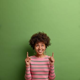 Positief etnisch vrouwelijk model trekt je aandacht naar boven, wijst met beide wijsvingers op lege ruimte, stelt voor om te klikken of te abonneren, toont plaats voor promo