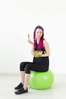 Positief gemengd ras hipster meisje met gekleurd haar dat een lichte griekse salade eet na fysieke training op een witte achtergrond. het concept van goede voeding en gewichtsverlies. advertentie ruimte