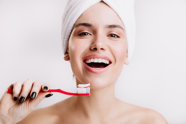 Positief gezond meisje doet ochtendbehandelingen voor schoonheid en hygiëne. vrouw met witte handdoek op haar hoofd poseren met tandenborstel.