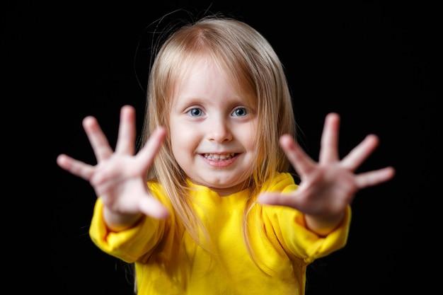 Positief glimlachend babymeisje in gele kleren