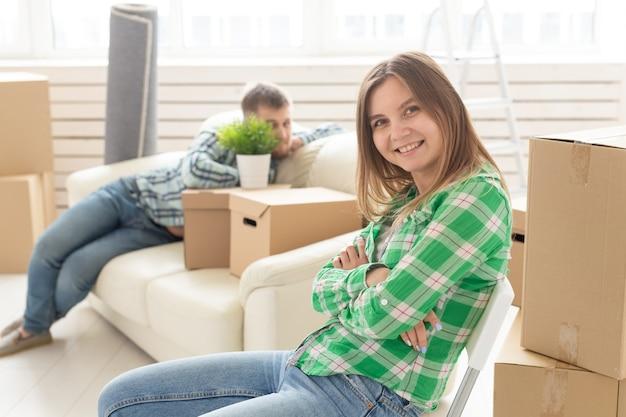 Positief glimlachend jong meisje zittend tegen haar lachende wazig echtgenoot in een nieuwe woonkamer tijdens het verhuizen naar een nieuw huis. het concept van vreugde door de mogelijkheid om nieuwe huisvesting te vinden.