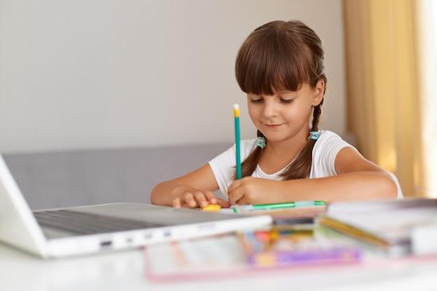 Positief, goed uitziend schoolmeisje dat casual kleding draagt, in oefenboek schrijft, een positieve stemming heeft, aan tafel zit in de woonkamer, online onderwijs.