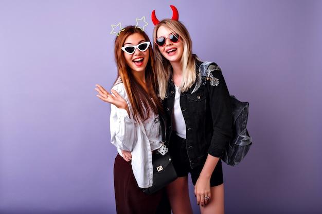 Positief grappig portret van de mooie amerikaanse vrouwen die genieten van hun feest, hipster-kleding voor jongeren, gekke zorgeloze, gemakkelijke stemming, twee beste vriendenmeisjes.