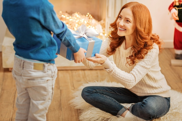 Positief ingestelde moeder lacht vrolijk terwijl ze met ogen vol liefde naar haar zoontje kijkt en een mooi ingepakt cadeau ontvangt.