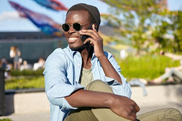 Positief jong mannetje met een donkere huid, breed glimlachend tijdens een gesprek met zijn beste vriend, sprekend over de smartphone terwijl hij buiten rust. mensen, communicatie, technologie concept