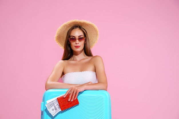 Positief jong meisje in strohoed en zonnebril met kaartjes en koffer roze studioachtergrond loo...