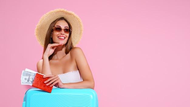 Positief jong meisje in strohoed en zonnebril met kaartjes en koffer roze studioachtergrond sm...