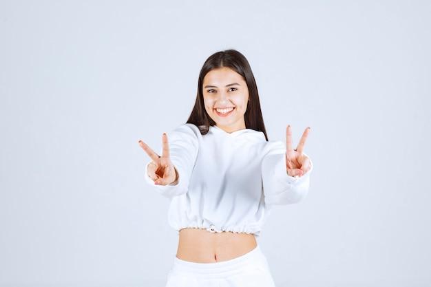 Positief jong meisjesmodel dat overwinningsteken toont.
