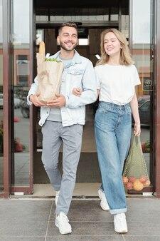 Positief jong stel in casual outfits met papieren zakken terwijl ze samen de supermarkt verlaten