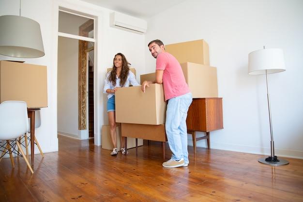 Positief jong stel kijkt uit over hun nieuwe appartement, terwijl ze binnen staan en leunen op kartonnen dozen en meubels