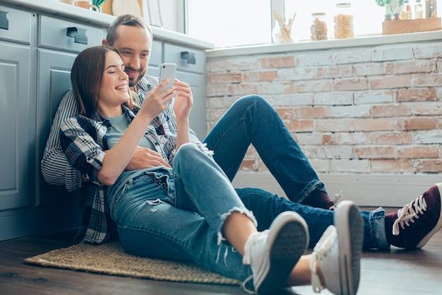 Positief jong stel knuffelen op de vloer in de keuken en kijken geamuseerd
