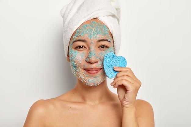 Positief jong vrouwelijk model met aangename glimlach, past natuurlijke scrub op gezicht toe, staat met naakt lichaam, houdt blauwe spons in de buurt van gezicht, ziet er gelukkig uit
