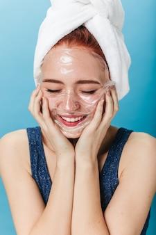 Positief kaukasisch meisje dat kuuroordbehandeling met glimlach doet. studio die van gelukkige vrouw is ontsproten die gezichtsmasker toepast dat op blauwe achtergrond wordt geïsoleerd.