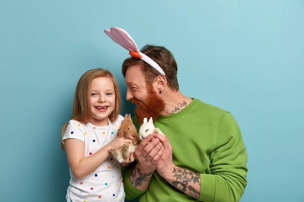 Positief kind en vader spelen met twee donzige konijnen