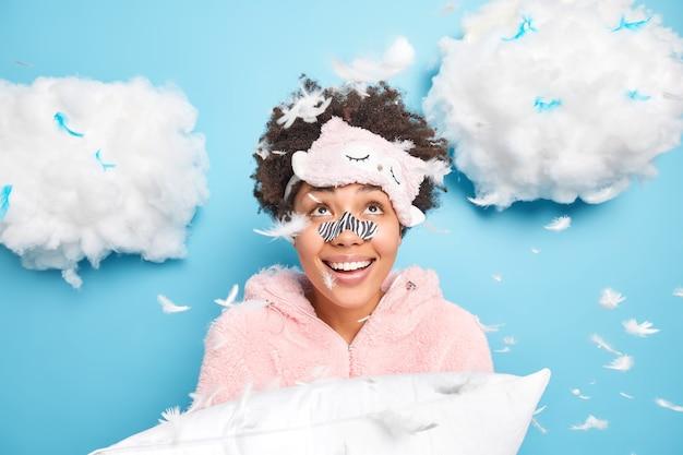 Positief krullend meisje draagt slaapmasker en pyjama houdt zacht kussen kijkt naar boven omringd met vliegende veren geïsoleerd over blauwe muur met wolken erboven