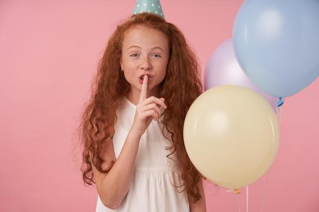 Positief krullend meisje met foxy lang haar in feestelijke kleding in hoge geest, camera kijken met wijsvinger op haar lippen, vragen om geheim te houden, geïsoleerd op roze studio achtergrond