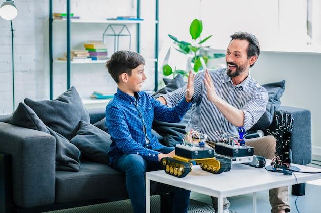 Positief lachende vader en zijn ingenieuze zoon besteden tijd aan robottechnologieën terwijl ze thuis rusten