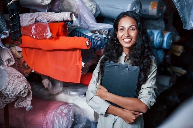Positief lachende werknemer met notitieblok is in de opslag vol stof.