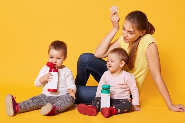 Positief liefhebbende moeder zorgt voor haar tweelingdochters, zit op de grond en is blij om tijd door te brengen met kleine baby's.