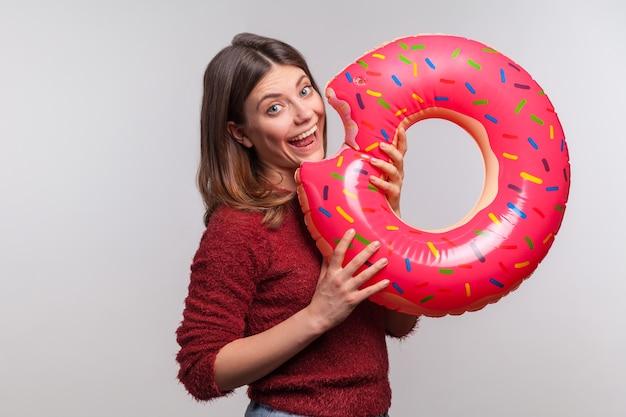 Positief meisje dat opblaasbare grote donut bijt, doet alsof ze een rubberen ring eet, plezier heeft op vakantie