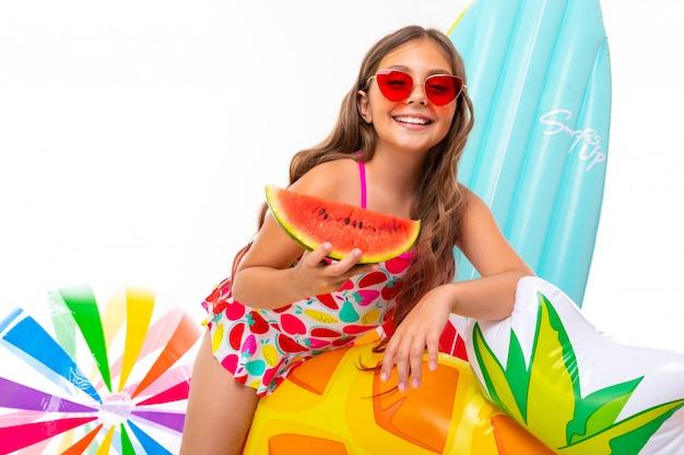 Positief meisje in een zwembroek met een brede glimlach op haar gezicht, zomervakantie, vers fruit