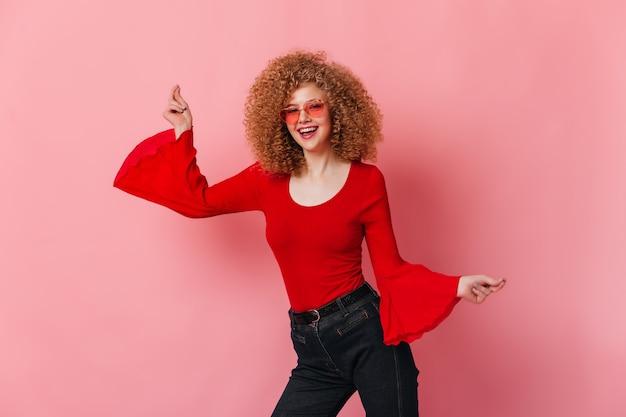Positief meisje in rode top met wijde mouwen en gekleurde glazen dansen op roze ruimte.