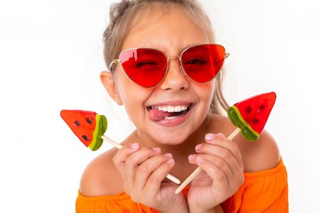 Positief meisje met een watermeloen-vormige lolly in haar handen, kijkend naar de camera in rode zonnebril, grimassen schattig